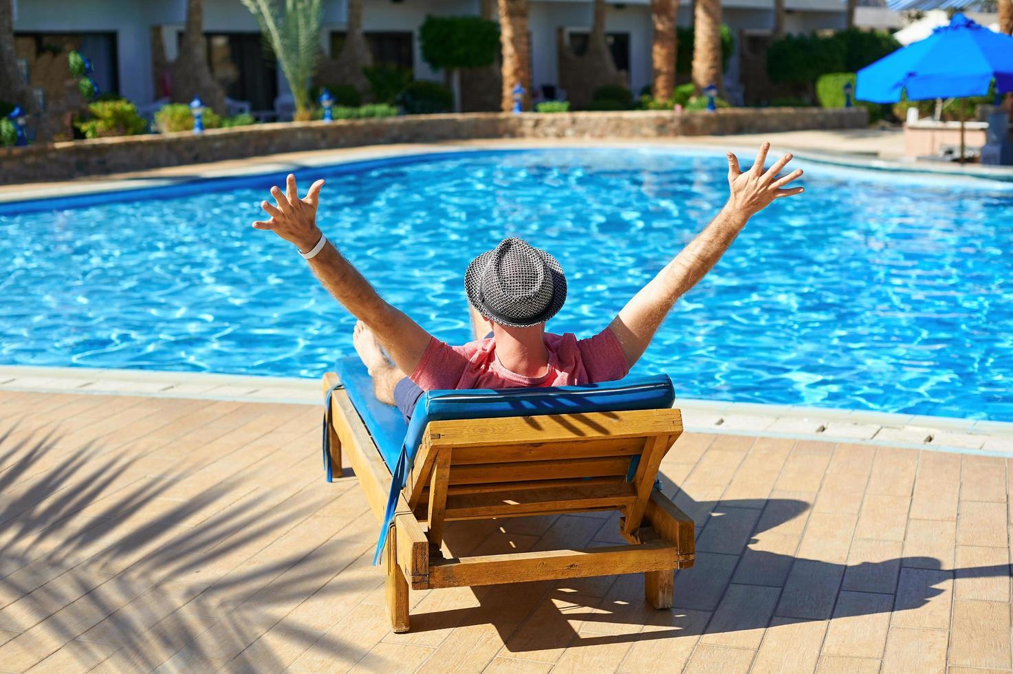 junger Mann, der auf einer Sonnenliege im Hotel liegt foto