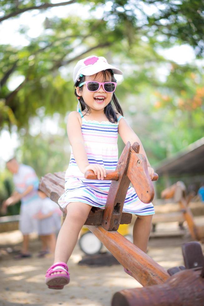junges asiatisches Mädchen auf Wippe foto
