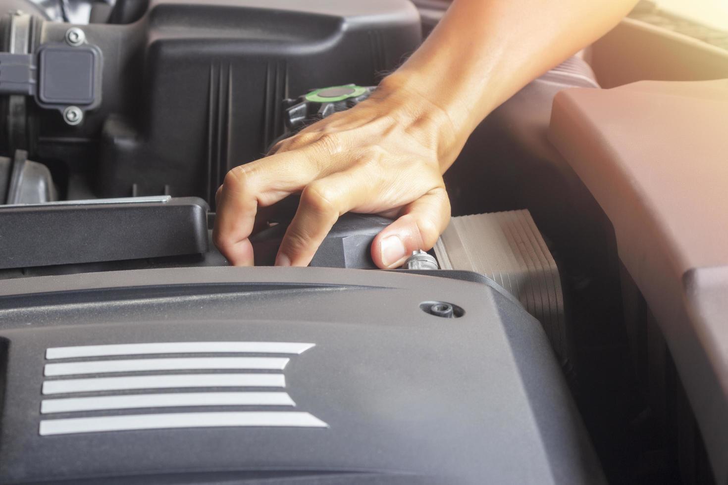 Hände des Mechanikers, der am Auto arbeitet foto