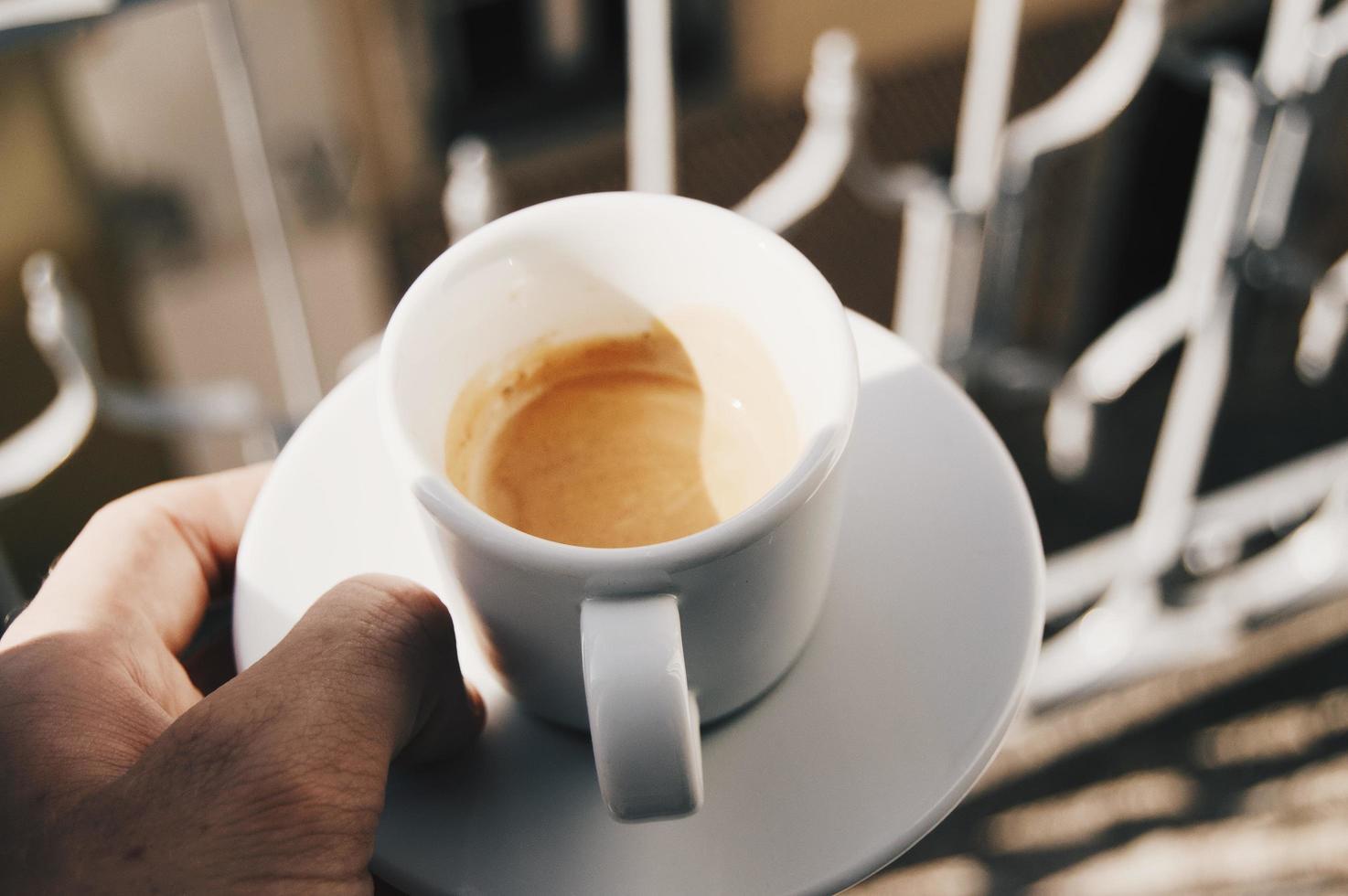 Mann hält Espresso foto