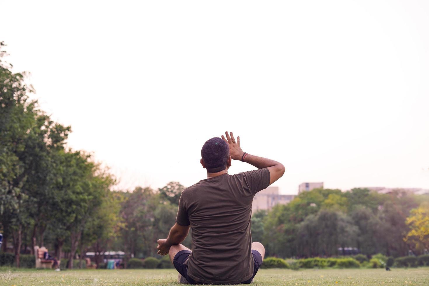 Mann, der Yoga in einem Park tut. foto