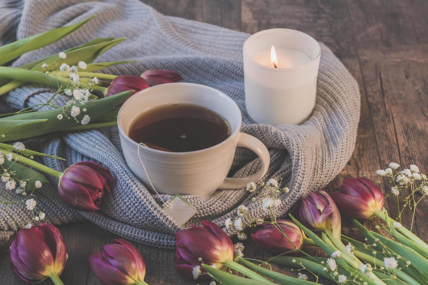 Tee, Tulpen und eine Kerze foto
