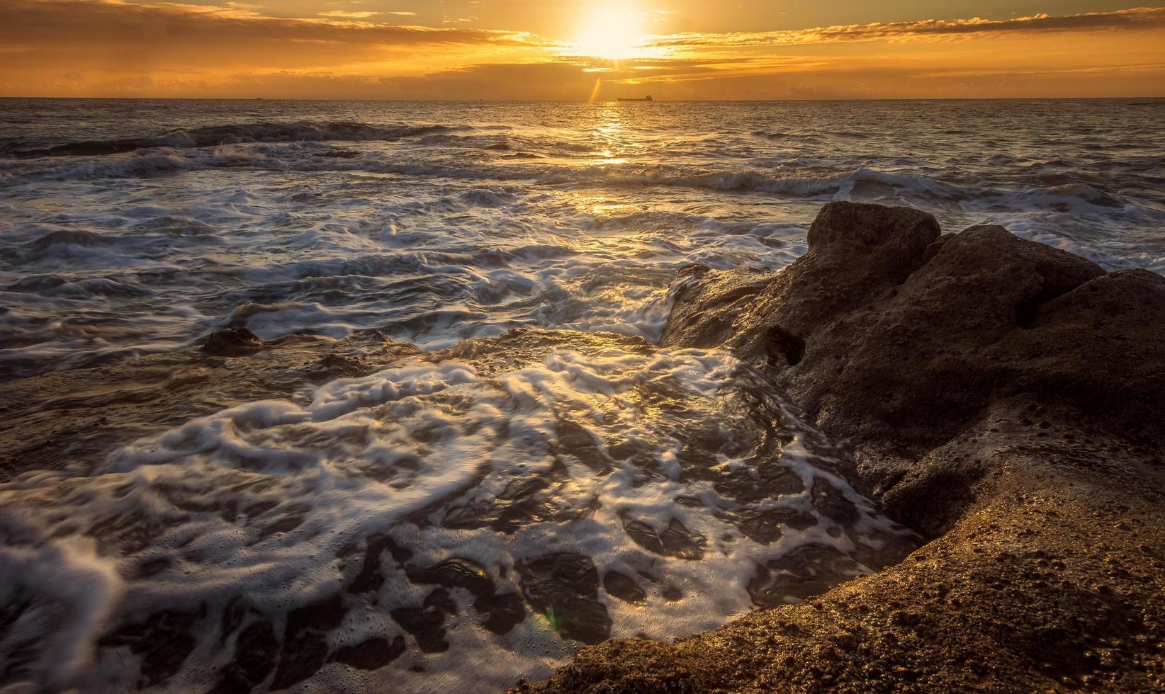 Ozeanwellen, die während des Sonnenuntergangs am Ufer abstürzen foto