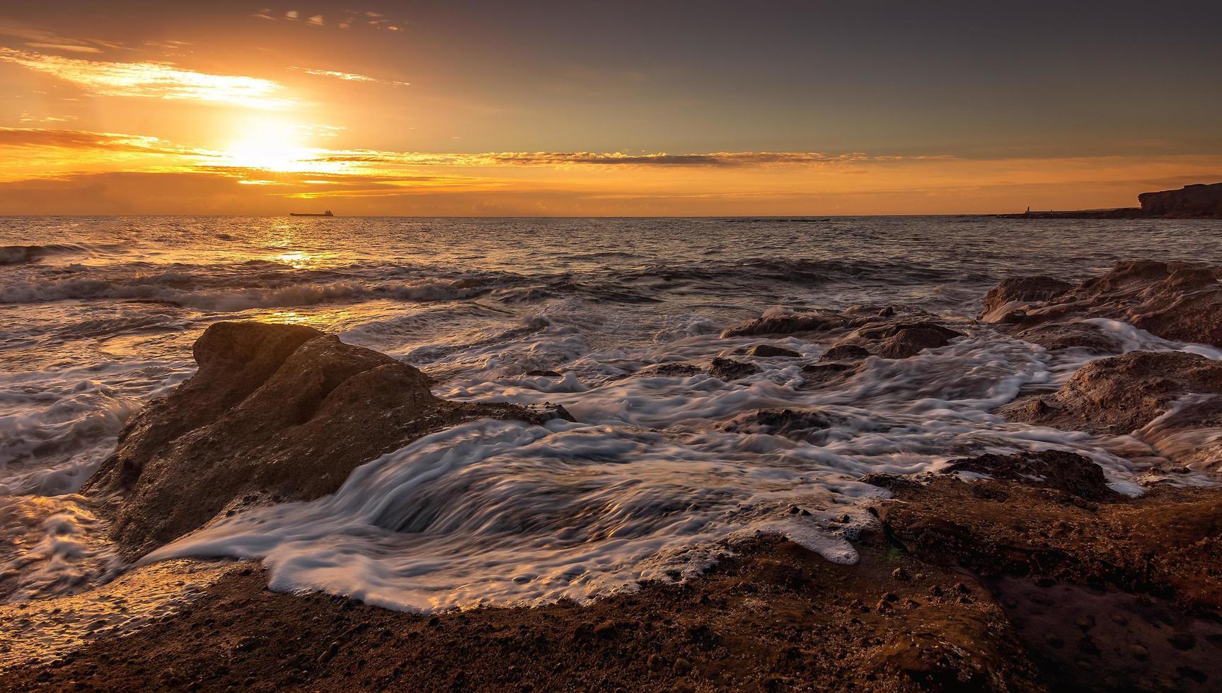 Wellen, die während des Sonnenuntergangs an Land krachen foto