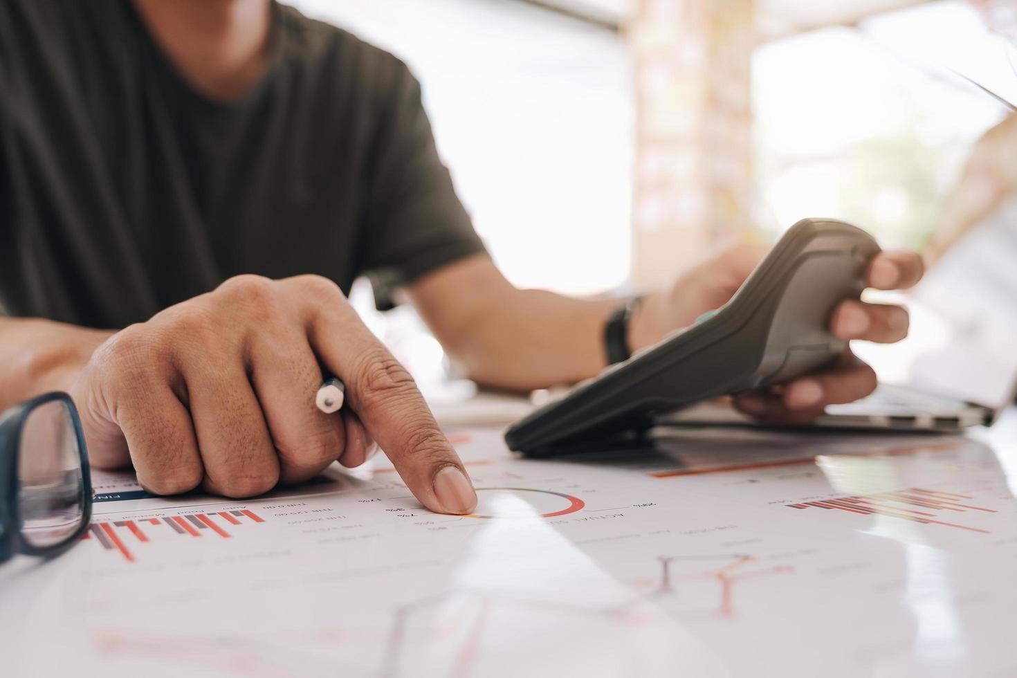 Geschäftsmann, der mit Rechner am Finanzdokument arbeitet foto