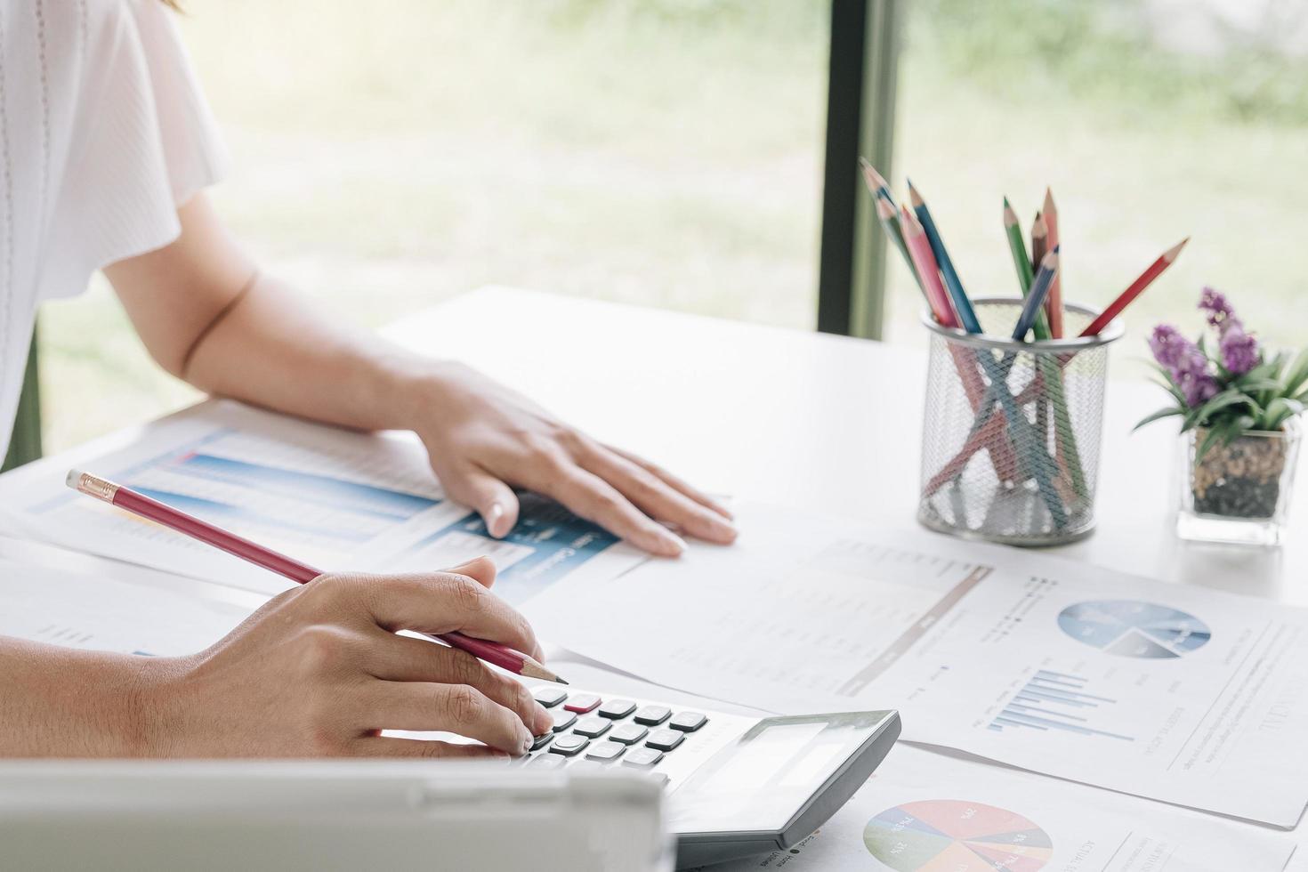 Geschäftsfrau mit Taschenrechner im Büro foto
