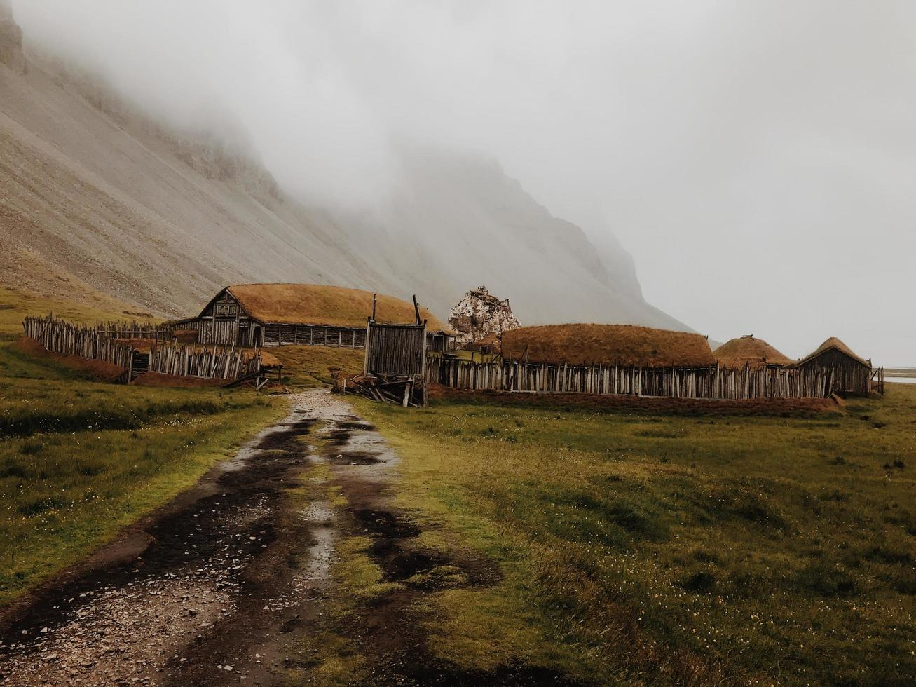 Hütte und Feldweg neben nebligen Berg foto