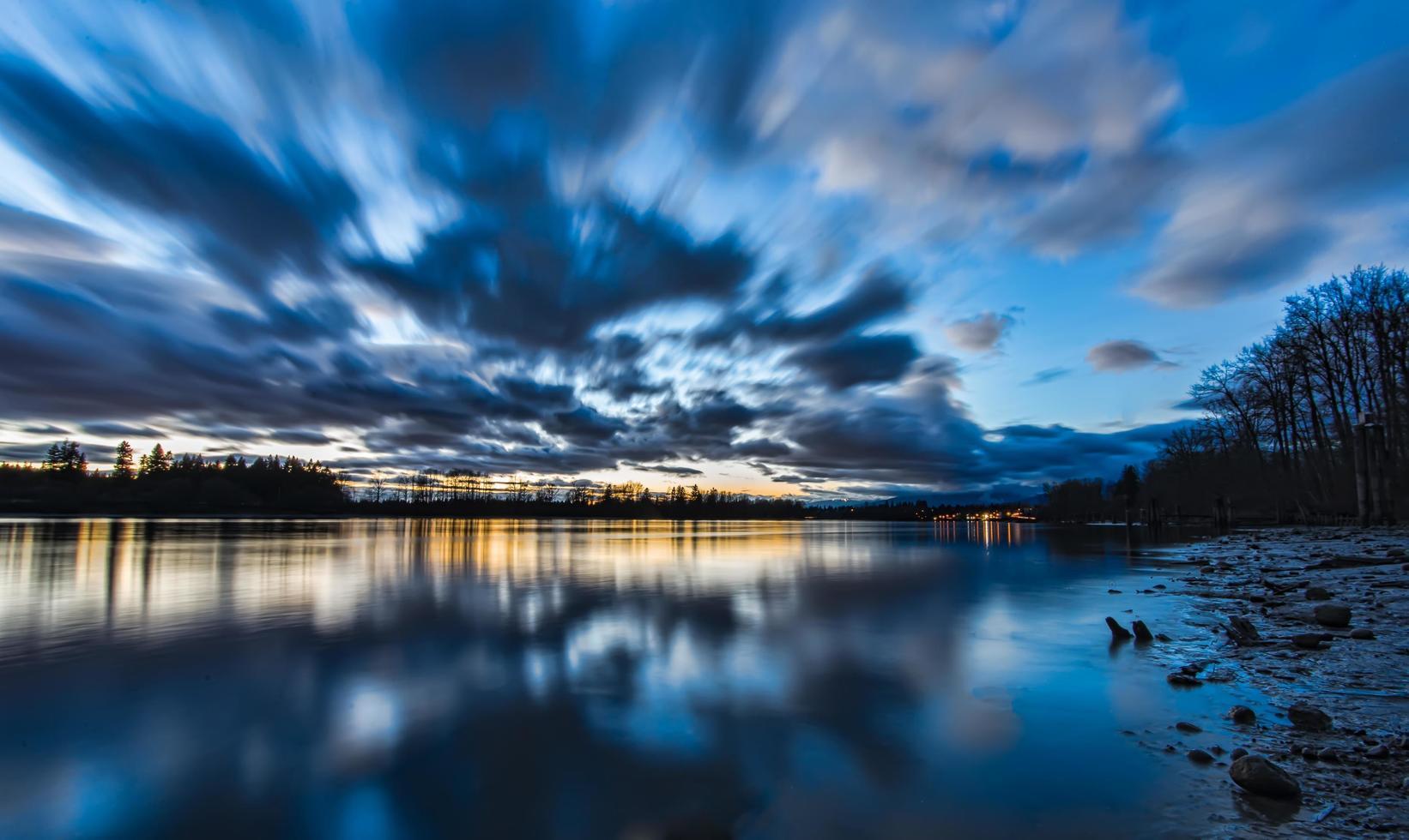 Zeitraffer der Wolken am See im Morgengrauen foto