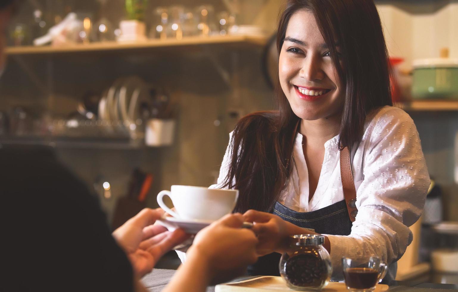 schöner Barista, der dem Kunden heißen Kaffee serviert foto