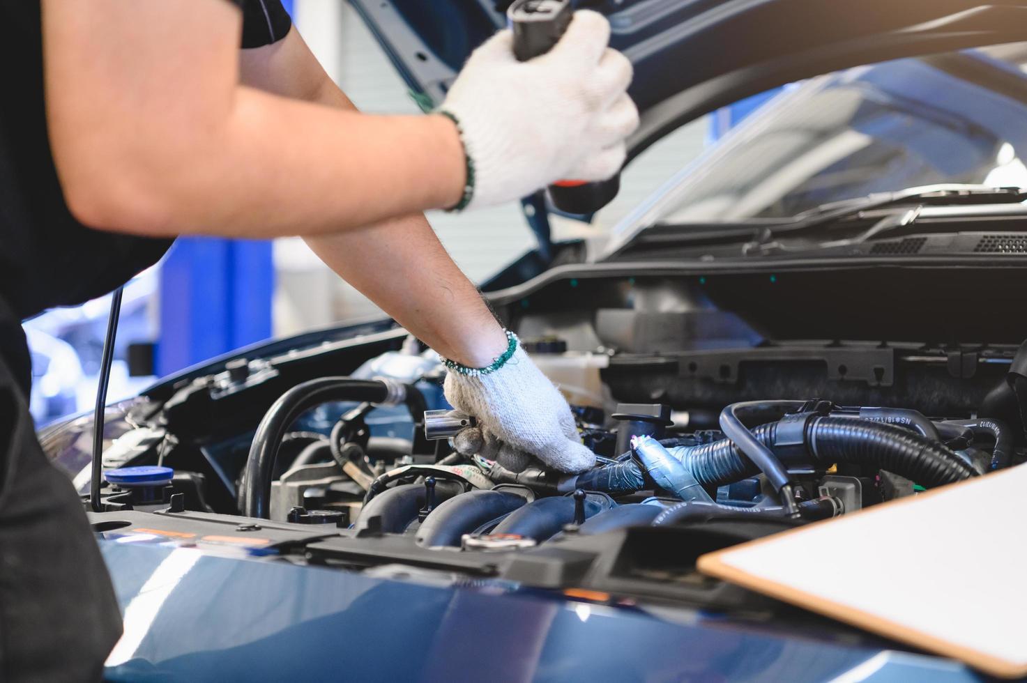 männlicher Mechaniker hält Taschenlampe, um Auto zu untersuchen foto