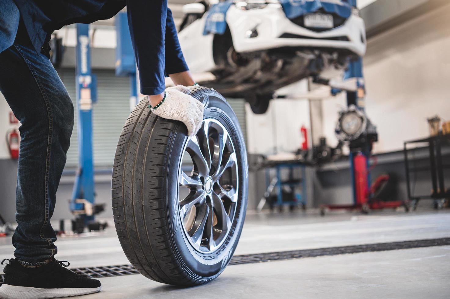 männlicher Mechaniker rollender Reifen foto