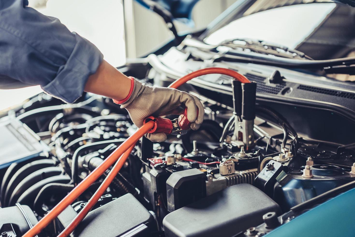 Automechaniker hält Überbrückungskabel foto