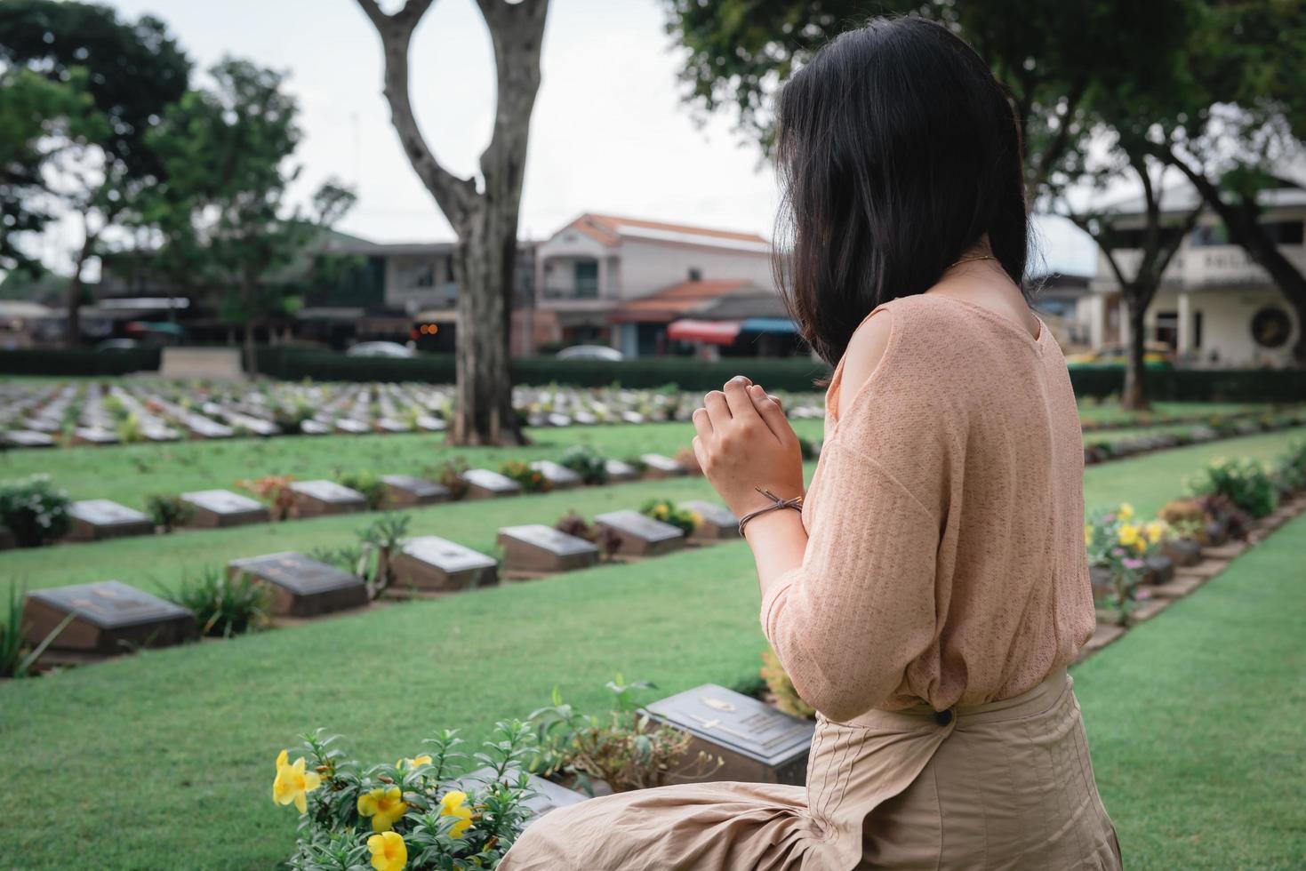Nahaufnahme der Frau, die am Friedhof betet foto