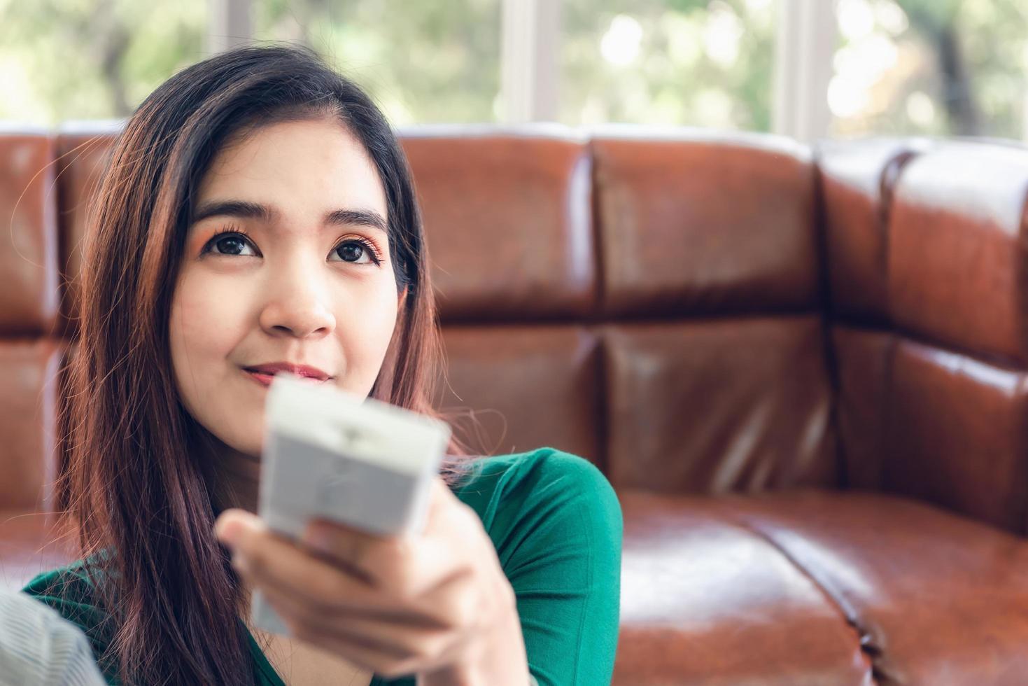 junge asiatische Frau zu Hause gesehen, die elektrische Klimaanlage steuert foto