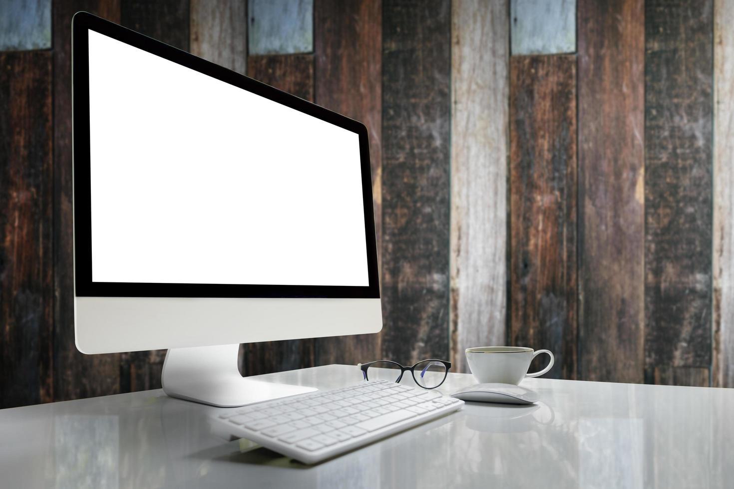 Computer mit leerem Bildschirm auf Tisch mit unscharfem Hintergrund foto