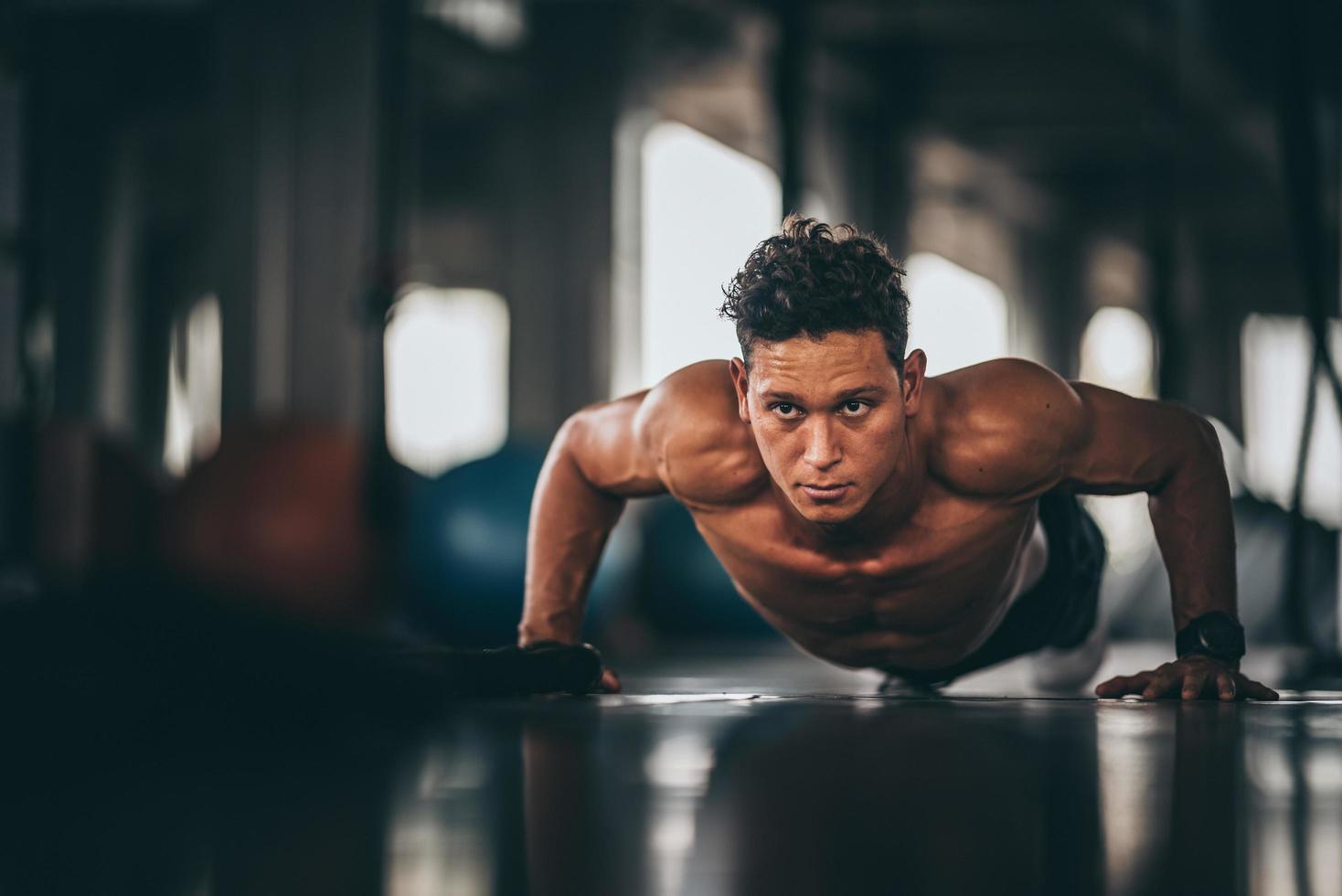 männlicher Athlet, der Liegestütze im Fitnessstudio tut foto