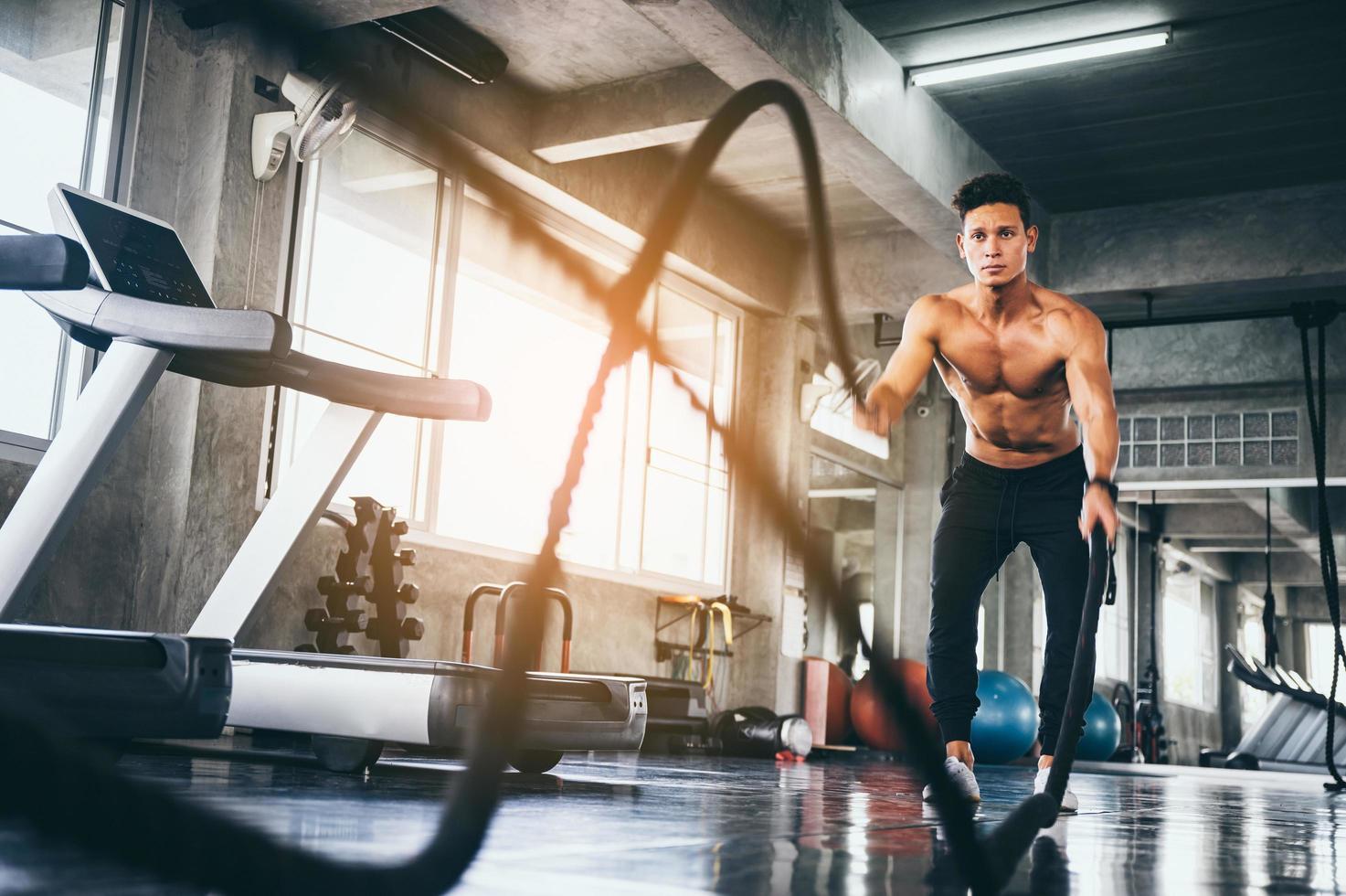 Mann trainiert mit Kampfseilen foto