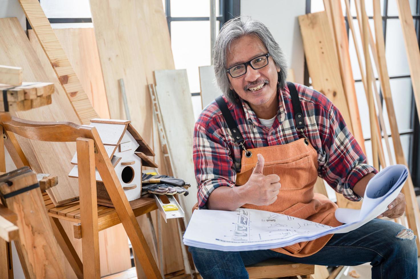 Zimmermann, der einen Daumen hoch hält, der Blaupause hält foto