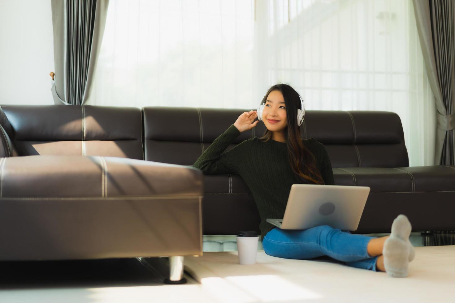 asiatische Frau, die Musik auf Laptop hört foto