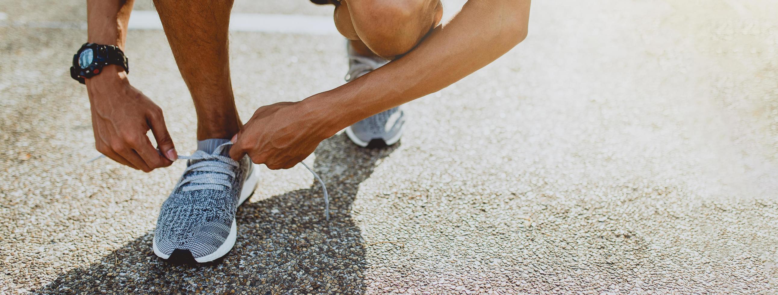 Mann, der Laufschuhe bindet, die sich zum Laufen bereit machen. gesunder Lebensstil und Sport. Banner mit Kopierplatz. foto