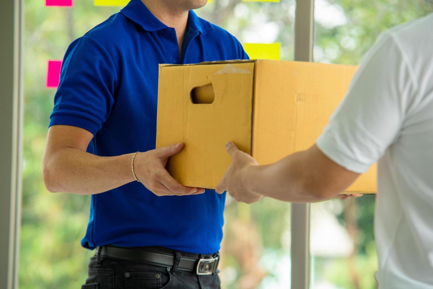 Der Postangestellte übergibt dem Kunden den Karton foto