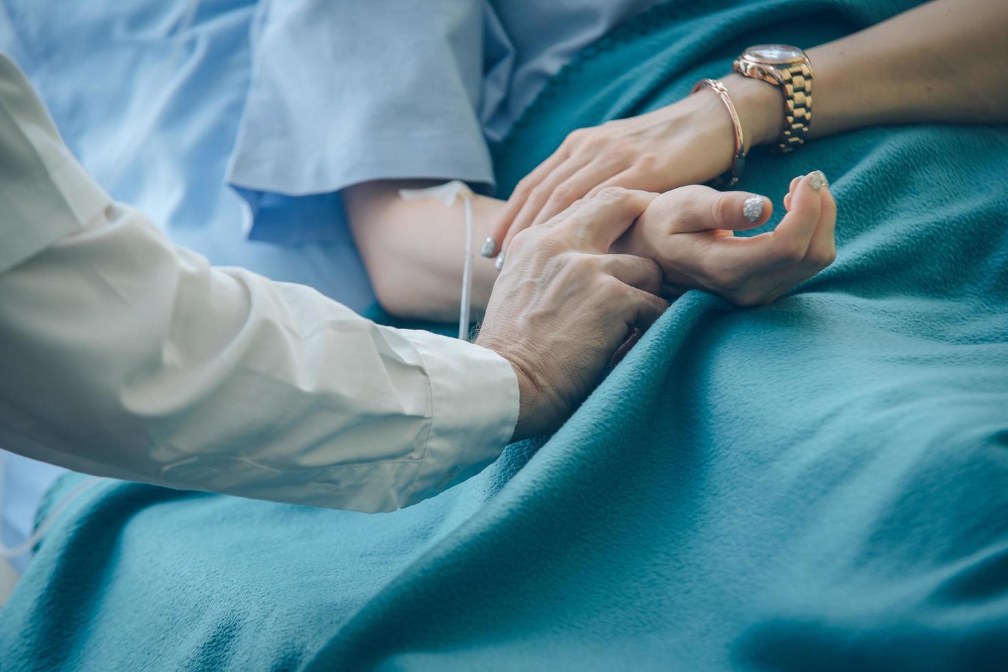 Arzt prüft auf den Puls des Patienten foto