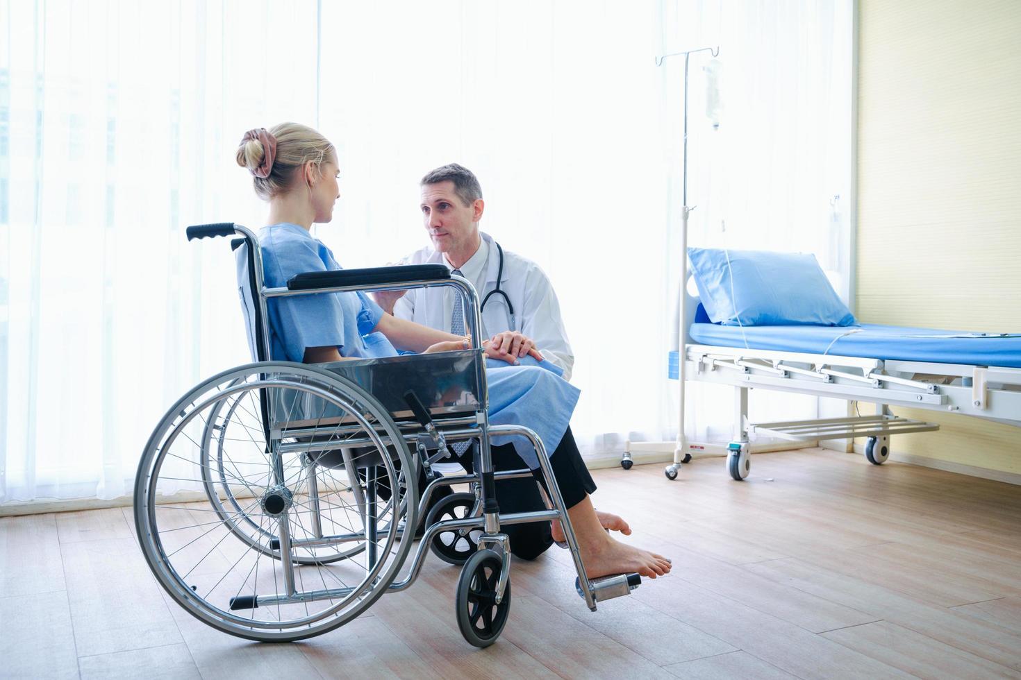 Ein Arzt spricht mit einem Patienten im Rollstuhl foto