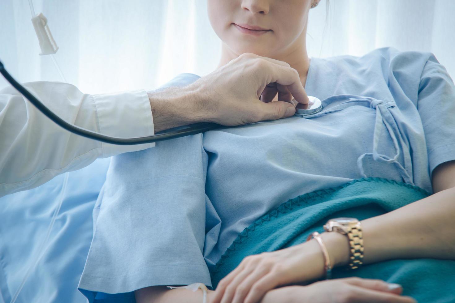 Arzt hört auf das Herz des Patienten foto