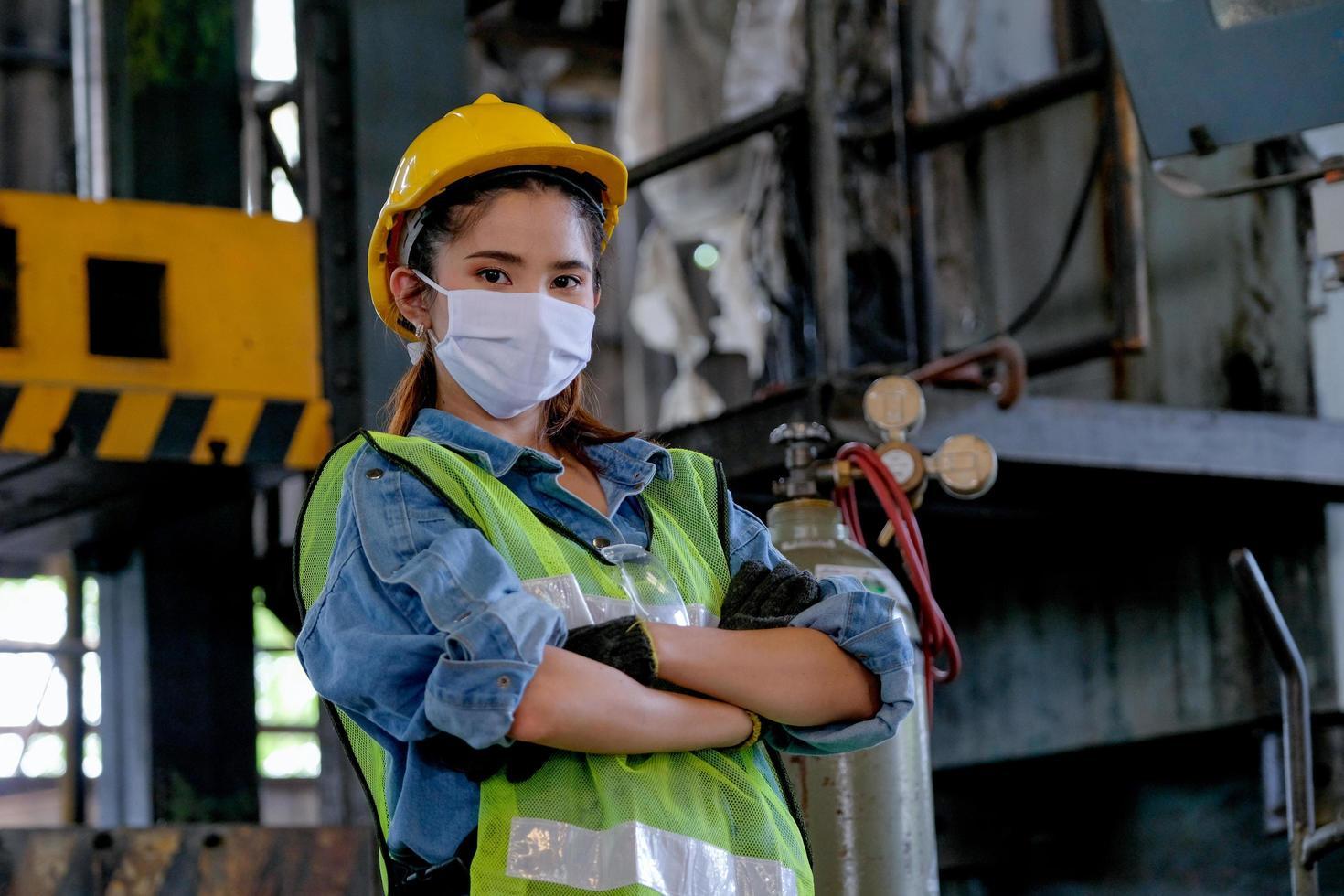 Fabrikfrau steht an ihrem Arbeitsplatz foto