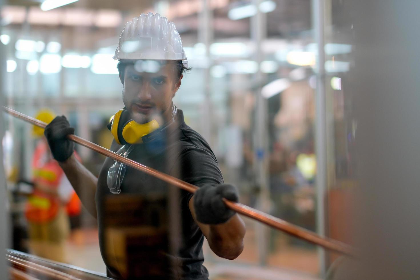 Techniker, der ein Kupferrohr am Fabrikarbeitsplatz hält foto