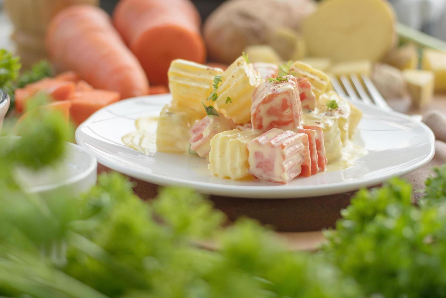 Kartoffelsalat auf weißem Teller mit Gemüse foto