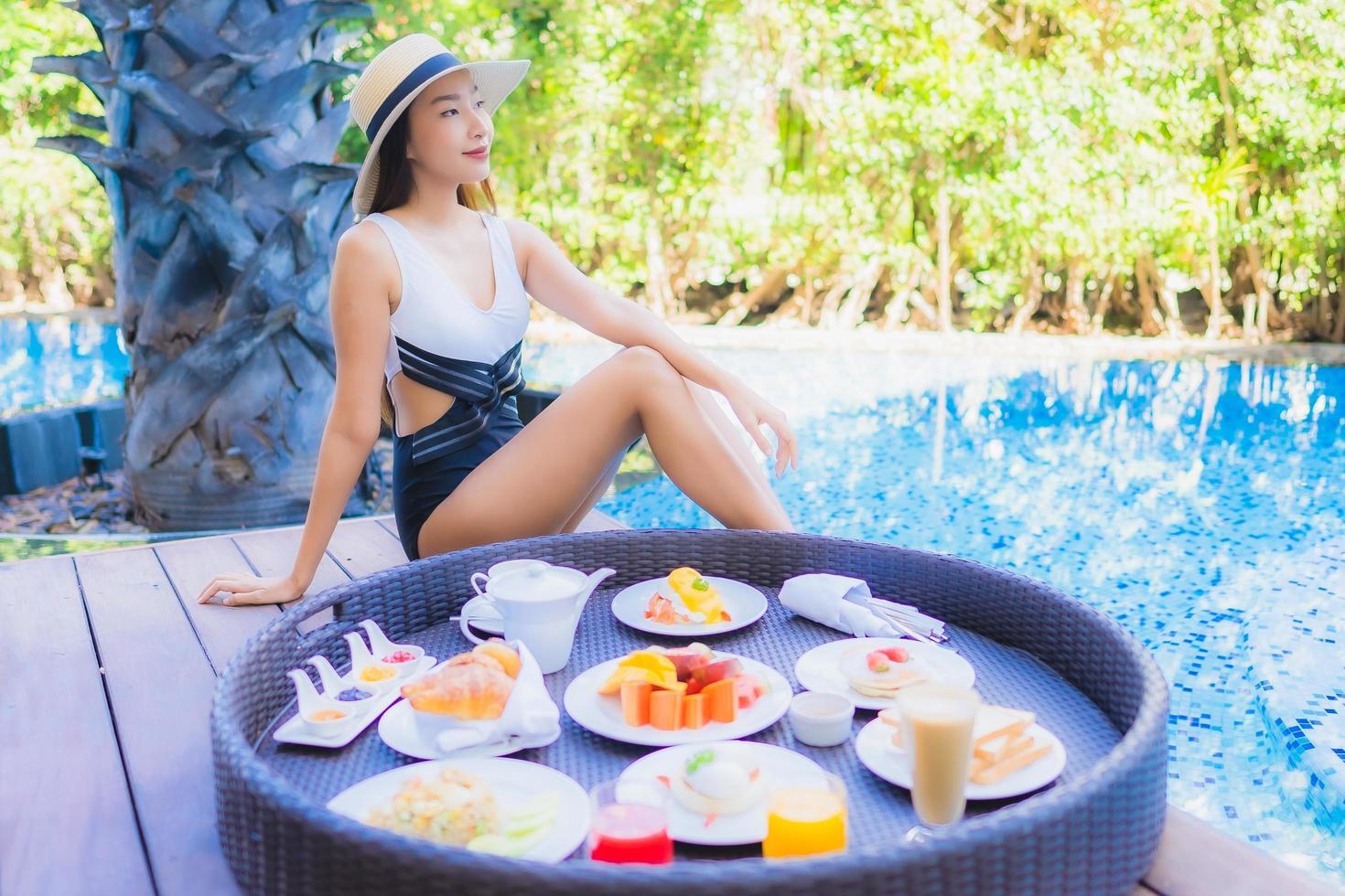 Frühstück auf schwimmendem Tablett mit lächelnder Frau im Hintergrund foto