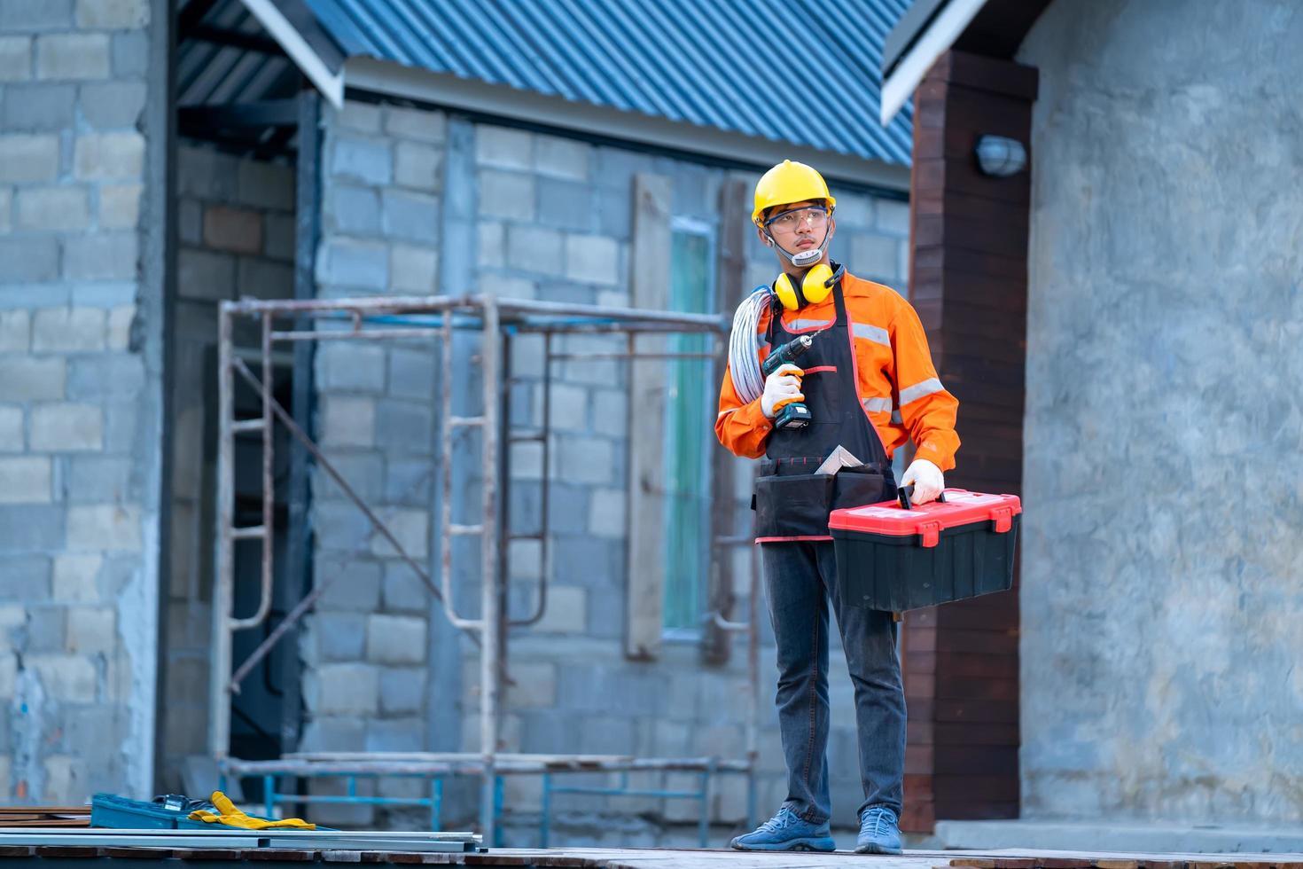 Bauarbeiter mit Bohrer und Werkzeugkasten foto
