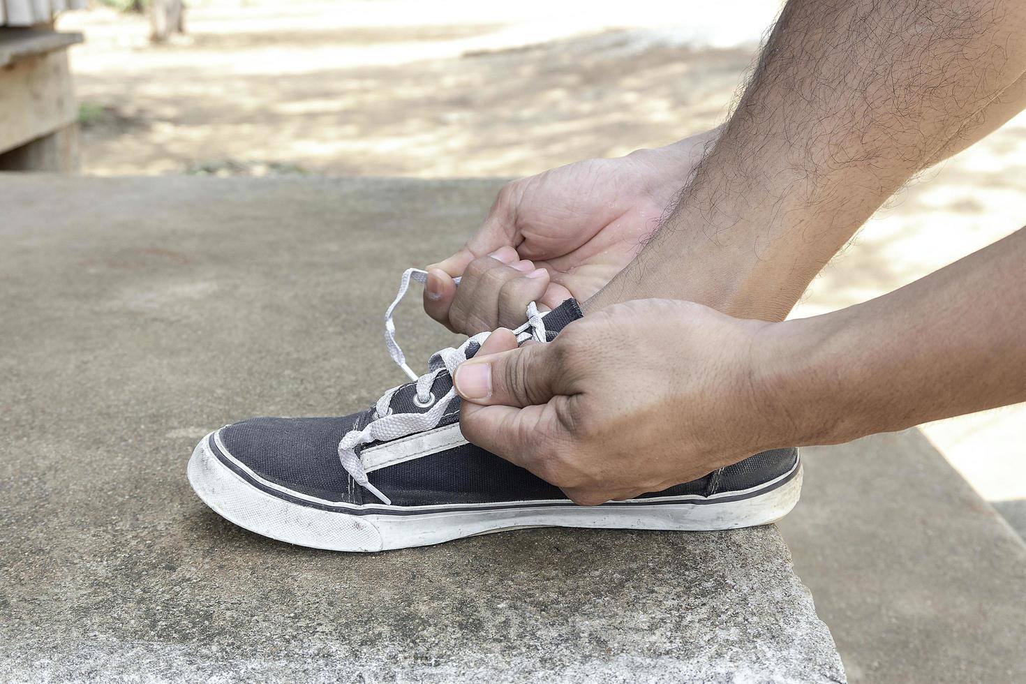 Person, die ihre Schuhe bindet foto