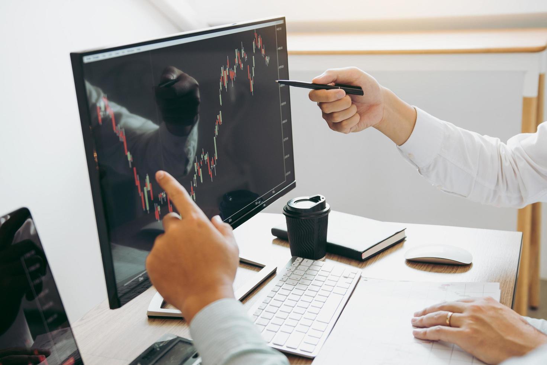 Zwei Geschäftsleute analysieren die Börse foto