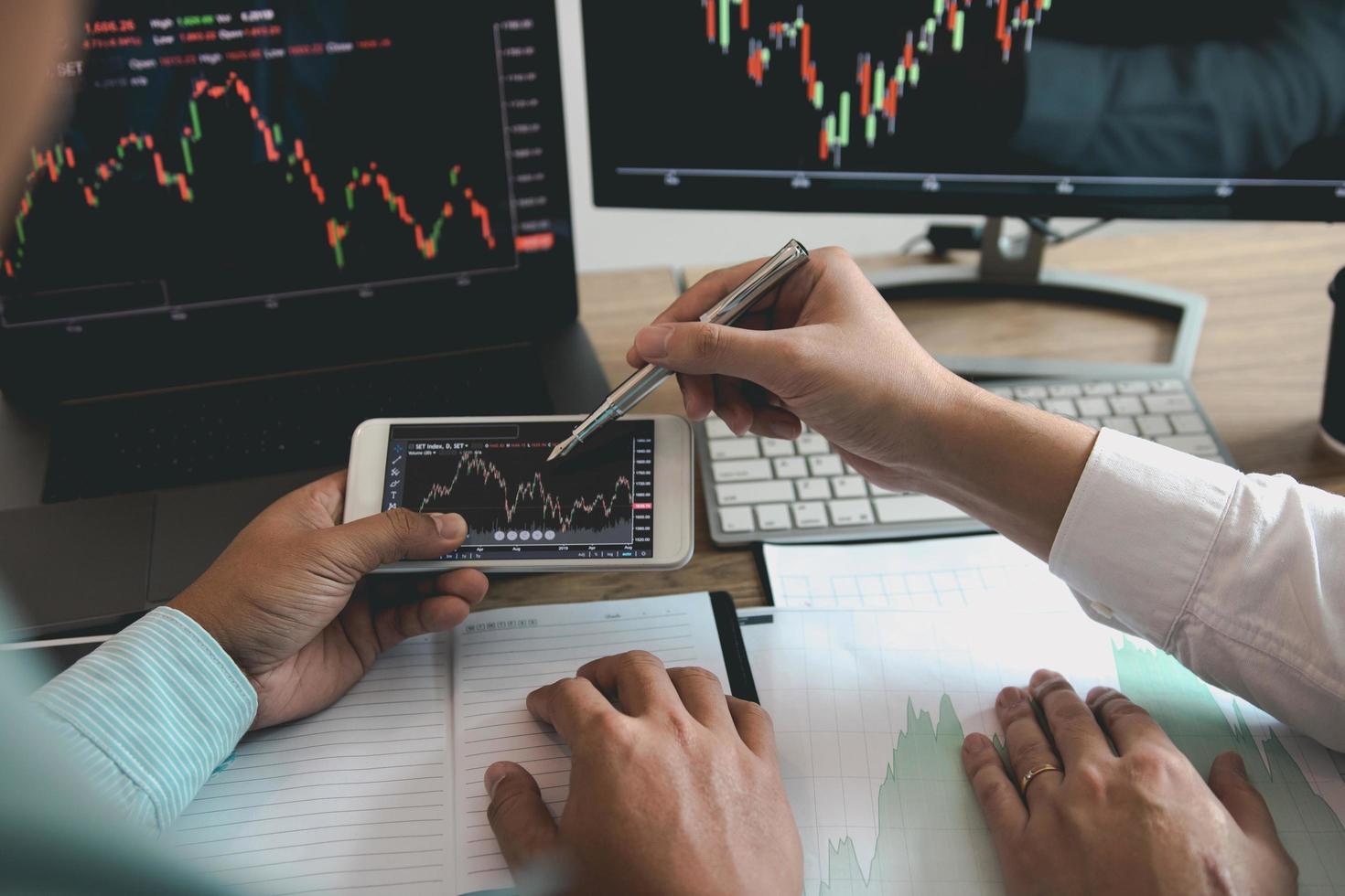 Zwei Investoren arbeiten zusammen, um Grafiken zu analysieren foto