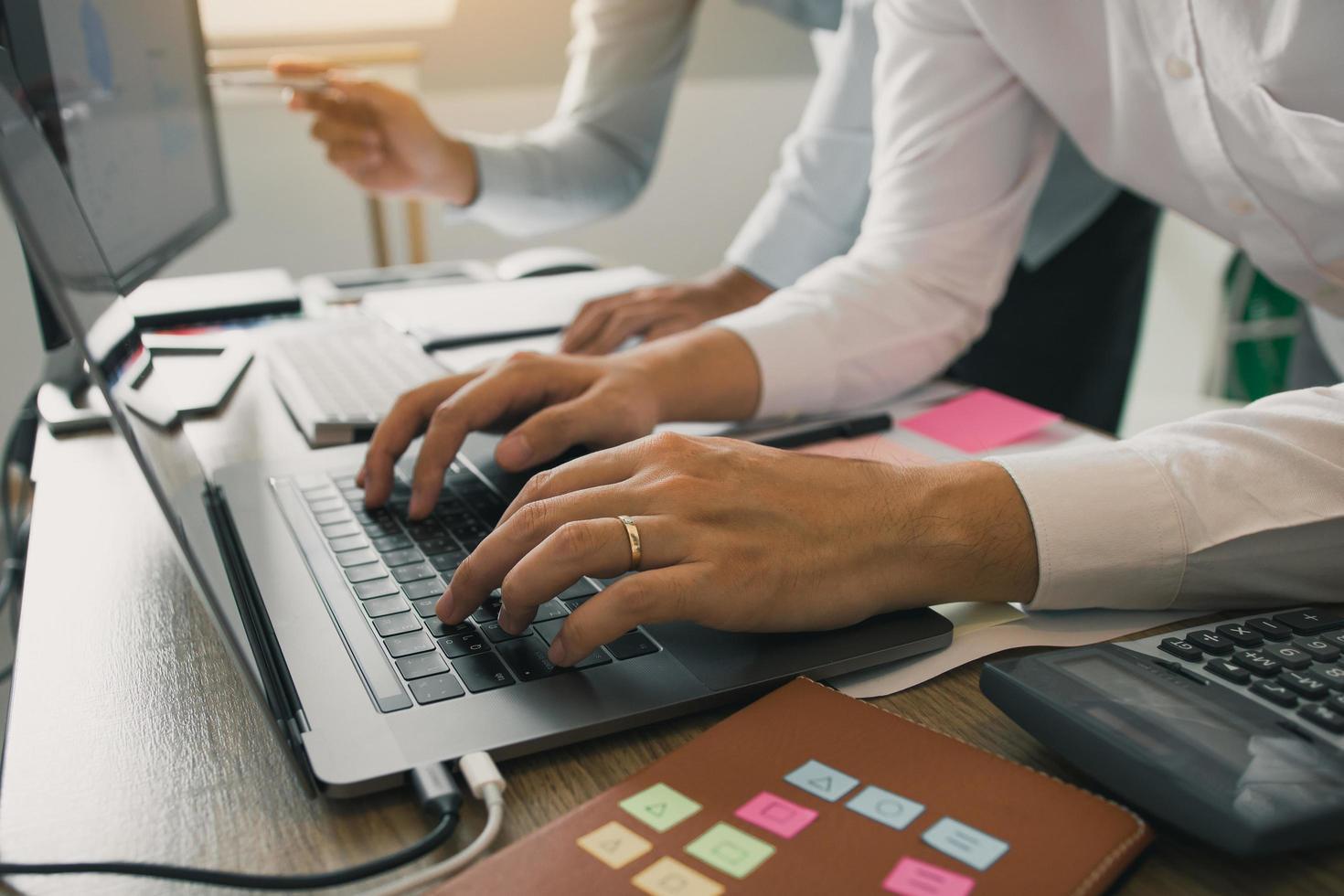 zwei Kollegen, die zusammen an Computern arbeiten foto