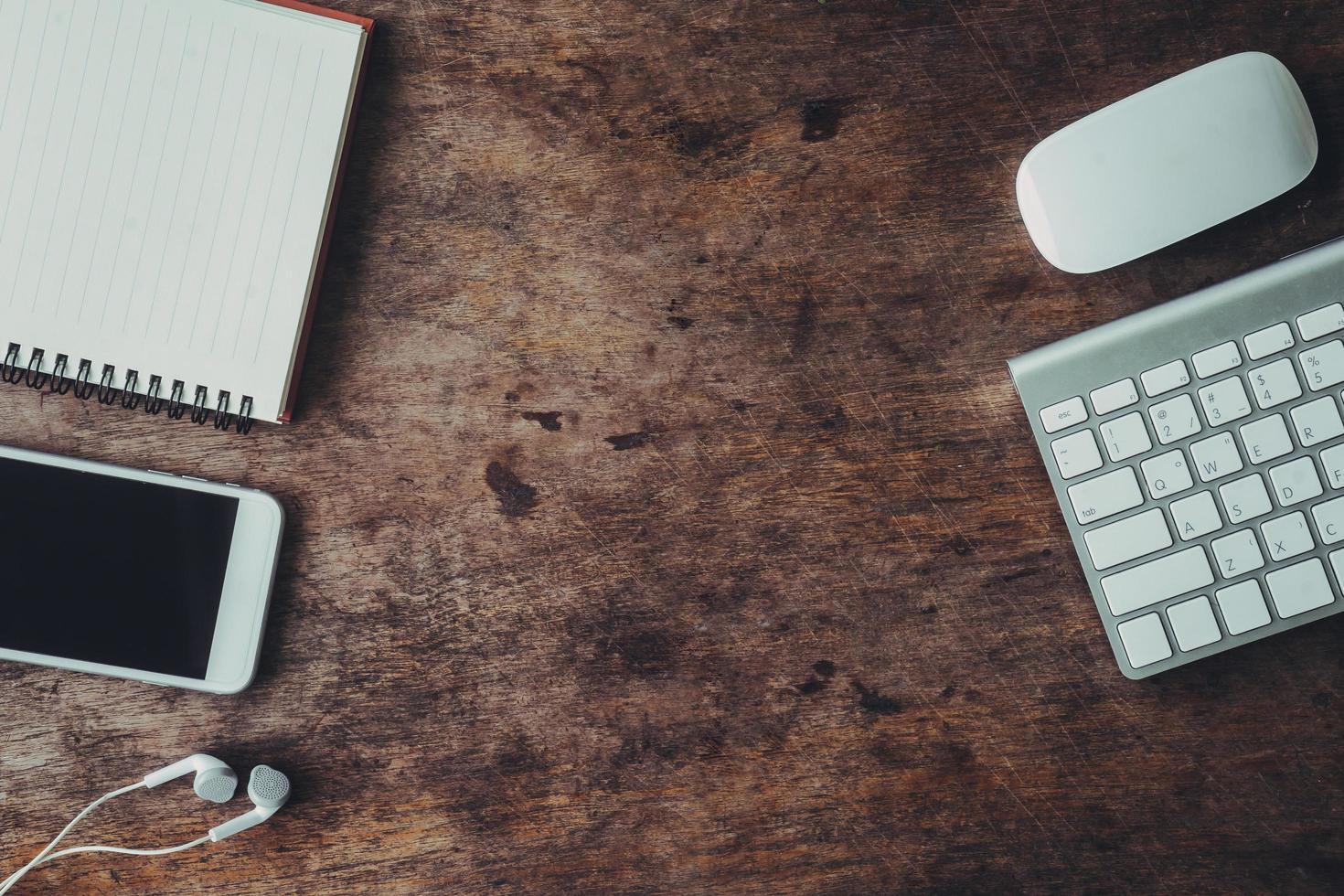 flache Schreibtischlage mit elektronischen Geräten und Notebook foto