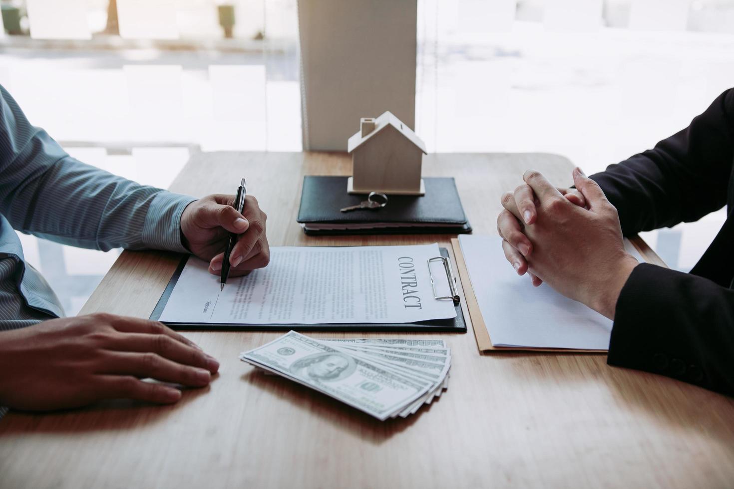neuer Hauskäufer unterschreibt Vertrag am Schreibtisch des Maklers foto