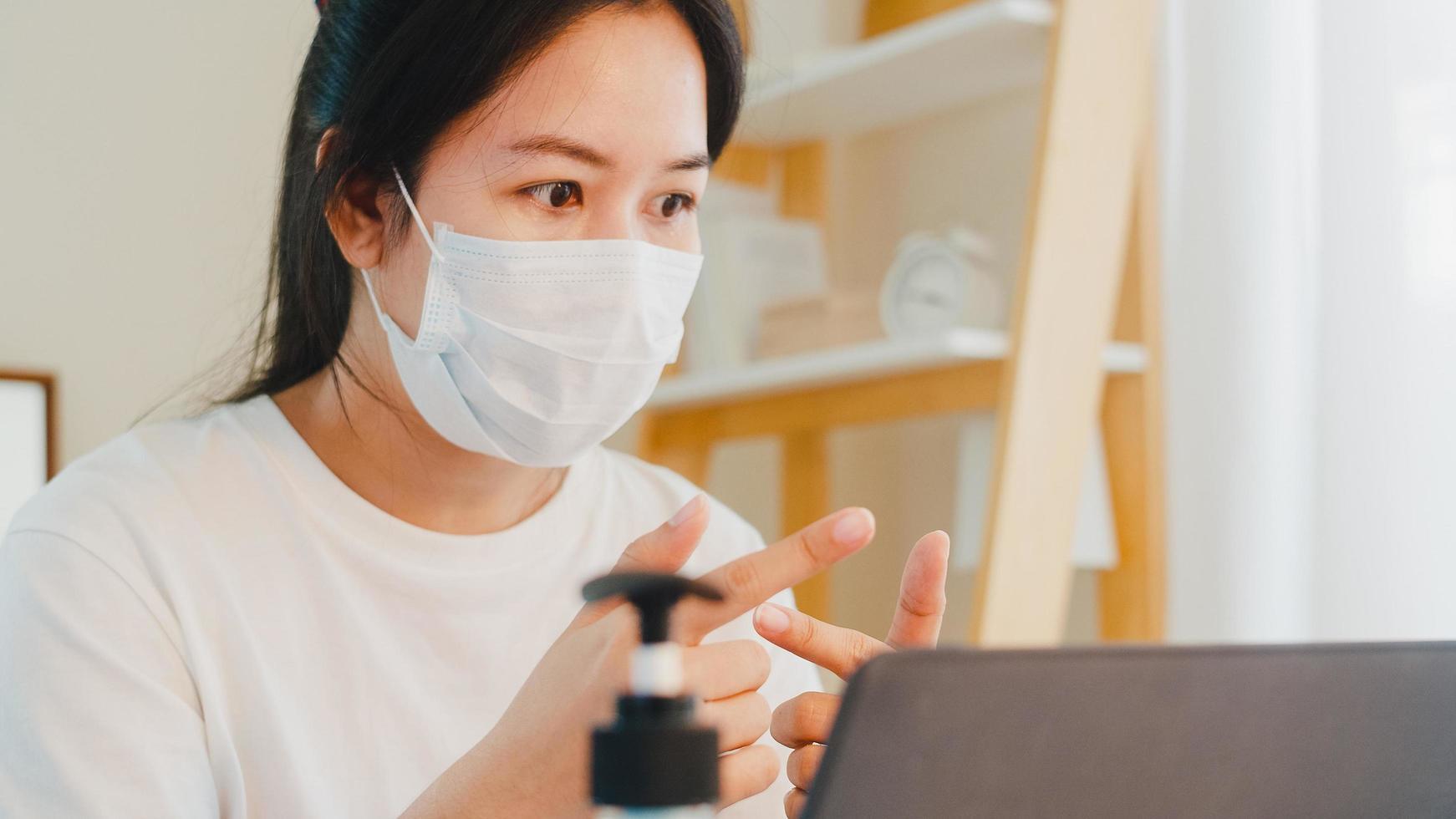 asiatische Geschäftsfrau, die Maske während des Videoanrufs zu Hause trägt foto