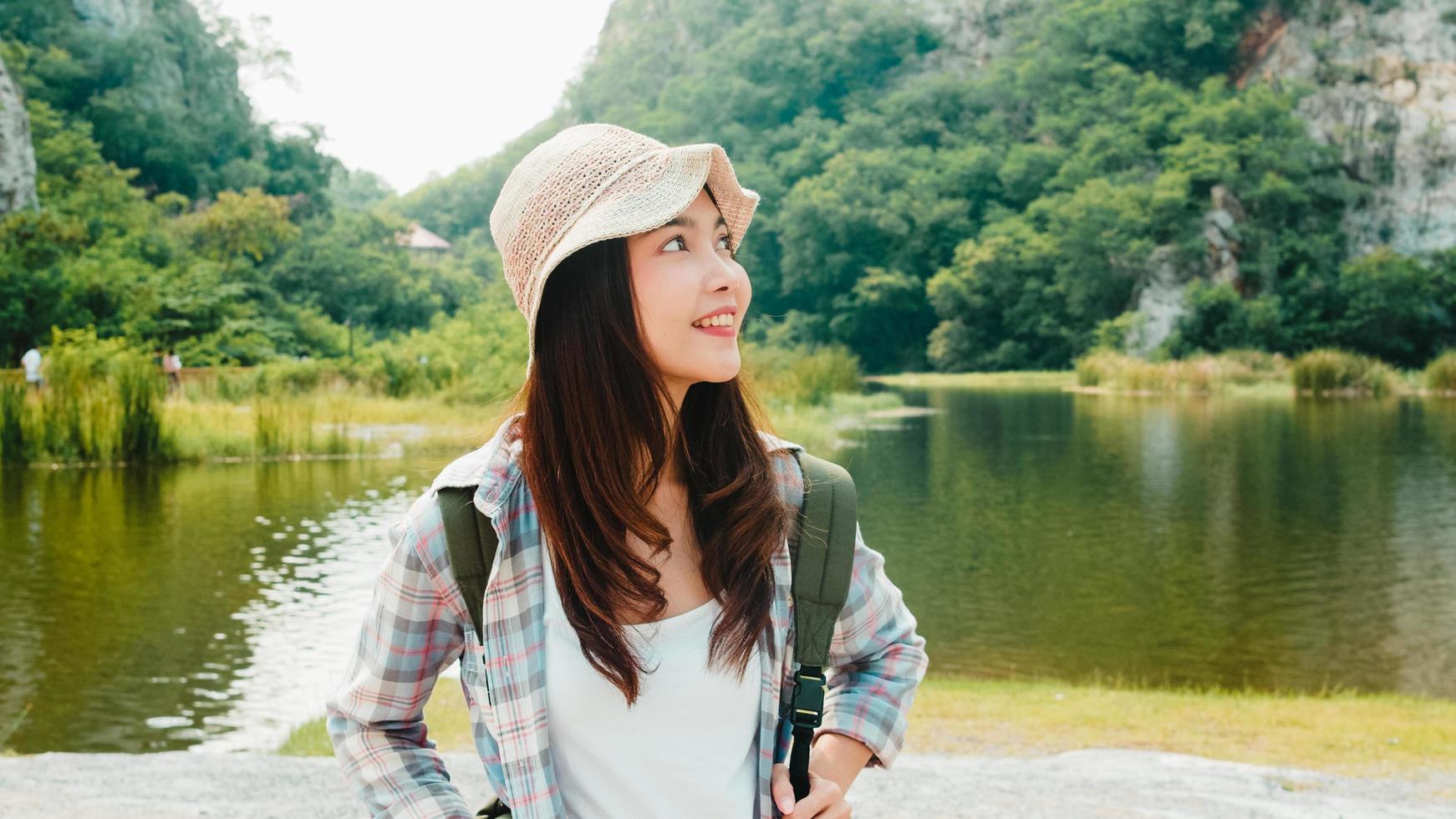 junger asiatischer Reisender mit Rucksack, der nahe Bergsee geht foto