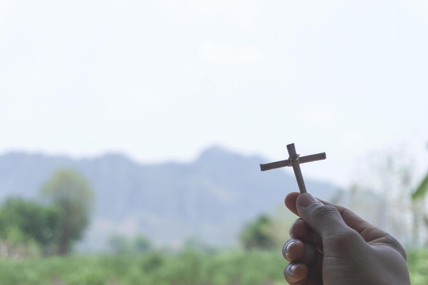 hausgemachtes Kreuz mit Bergen im Hintergrund foto