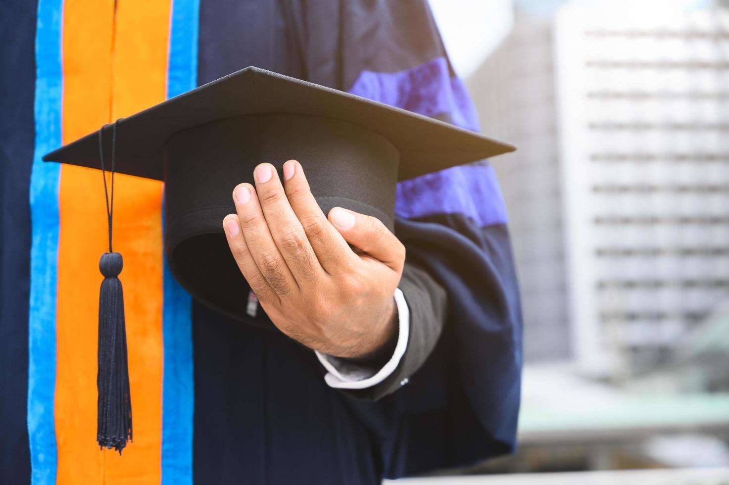 Nahaufnahme des Absolventen, der Abschlusskappe hält foto