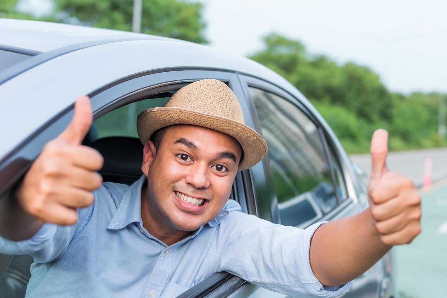 männlicher Fahrer, der Daumen aufgibt foto
