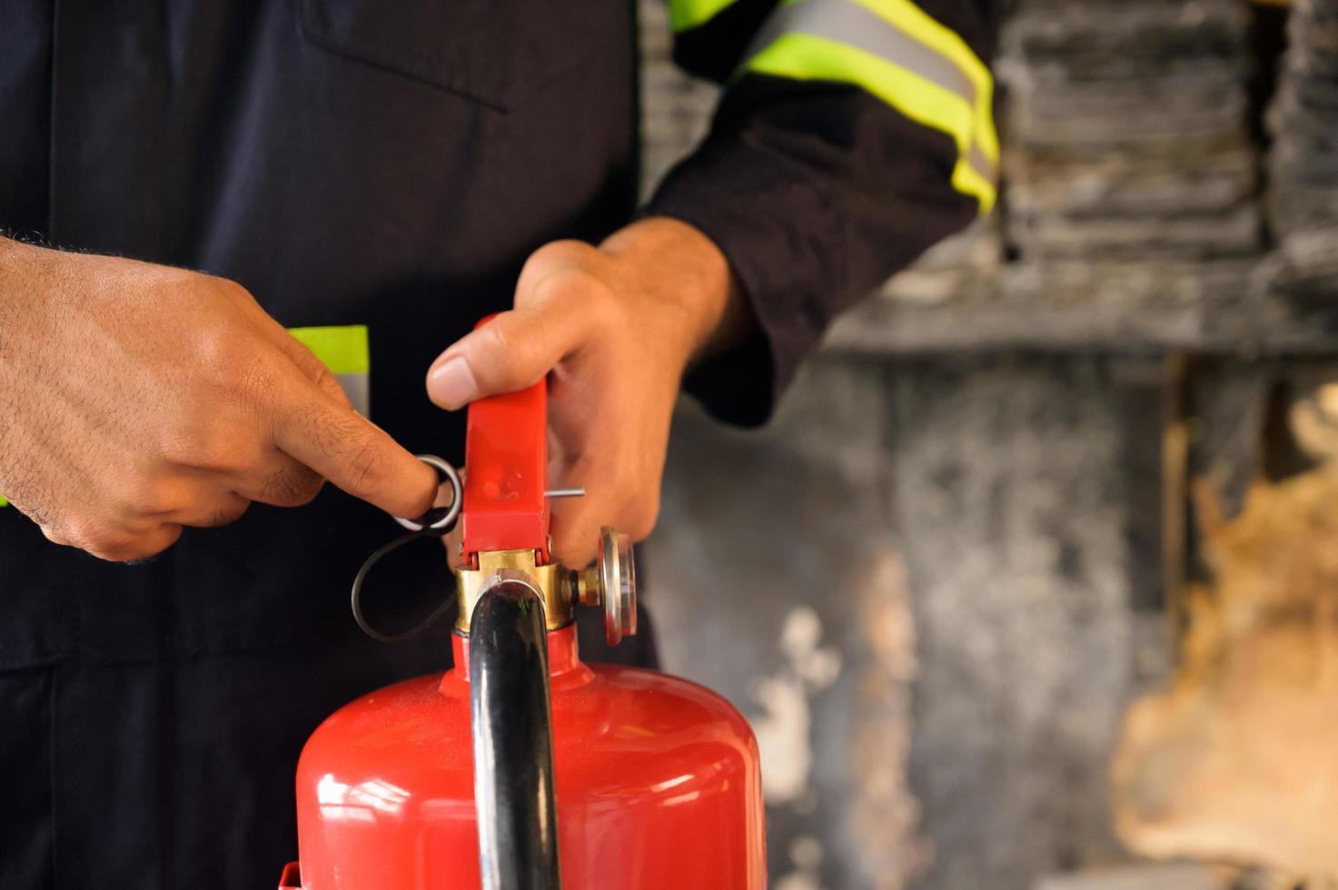 Nahaufnahme des Feuerwehrmanns, der Stift des Feuerlöschers zieht foto