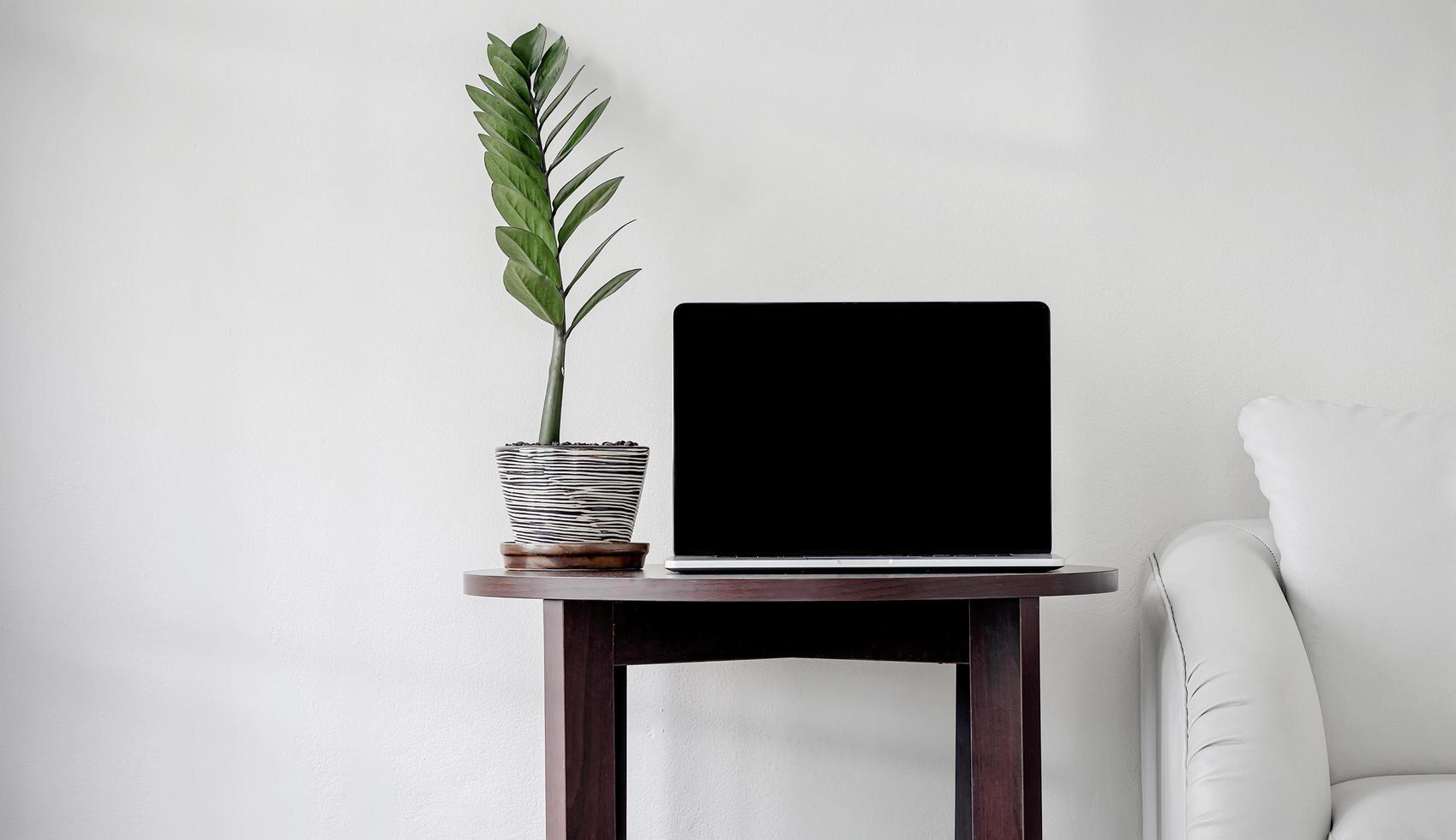 schwarzer Bildschirm Laptop auf minimaler weißer Wand foto