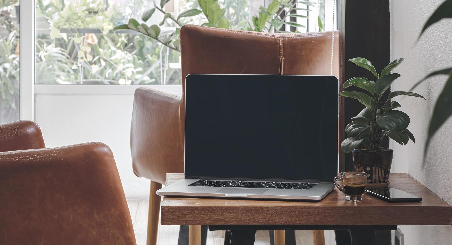 Laptop mit Espresso und Telefon im Wohnzimmer foto