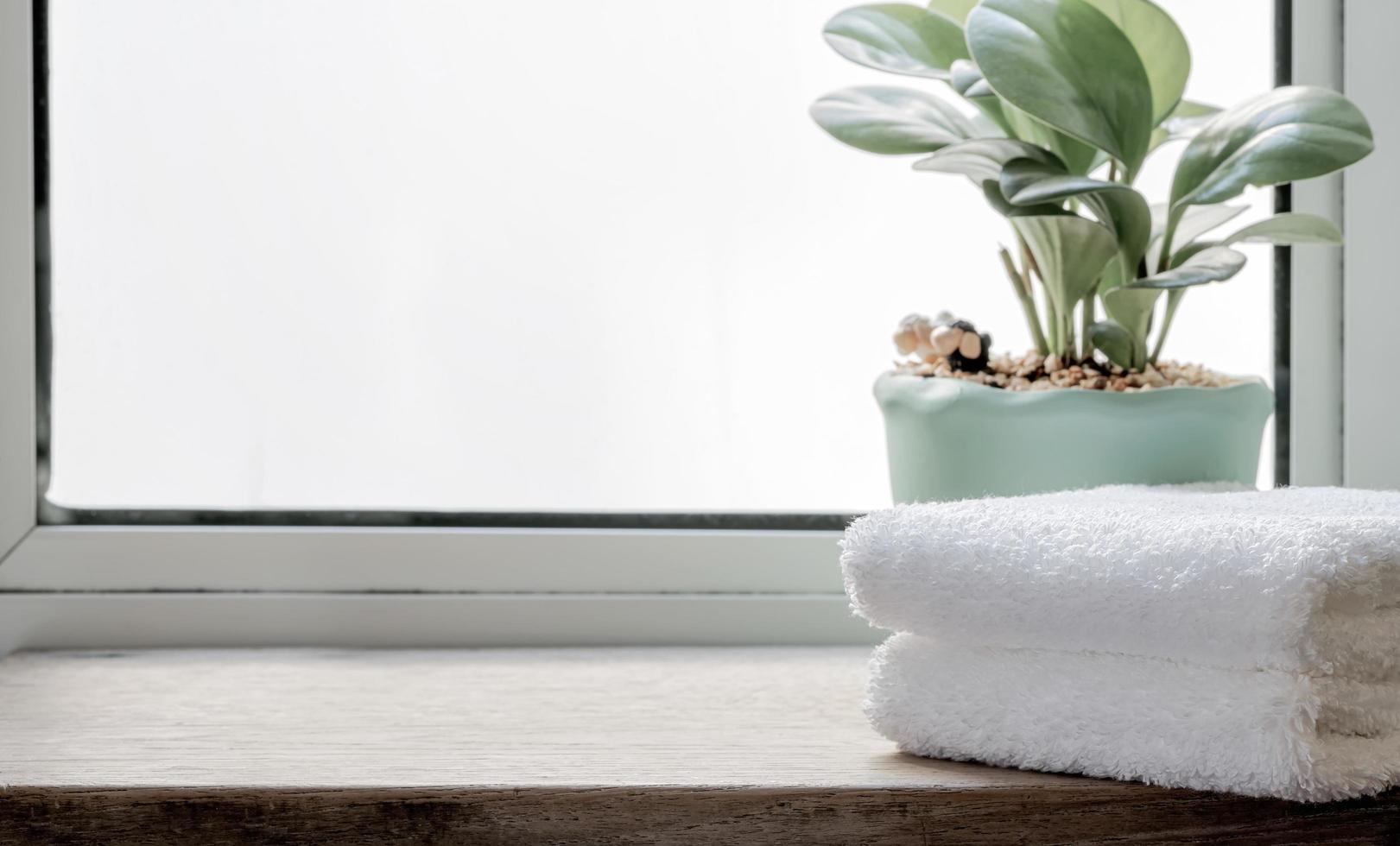 gefaltete saubere Handtücher mit Zimmerpflanze auf Holztisch foto