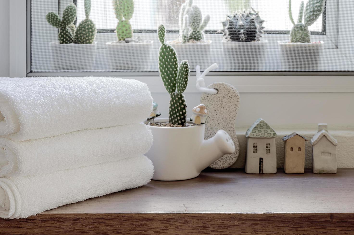 gefaltete saubere Handtücher mit Zimmerpflanze auf Holztheke foto