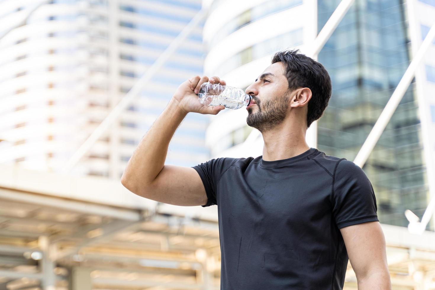 Mann trinkt Wasser in Flaschen foto